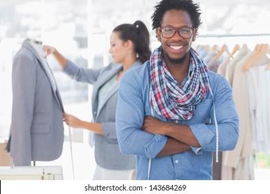 Fashion designer posing while his colleague is measuring blazer lapel behind
