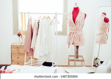 Fashion designer showroom studio workshop background with new collection of pink pastel female clothing design. Tailor and sewing concept. Dressmaker modern room interior red with mannequin
