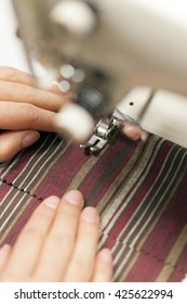Fashion designer or student is sewing details of her new dress for homework.