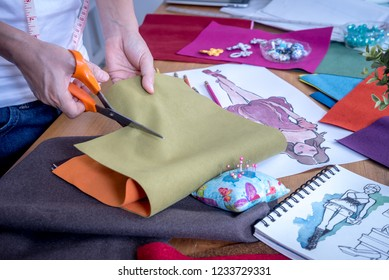 Fashion designer (tailoress) cutting fabric while working with drawing sketch, material  at worktable / Garment business concept