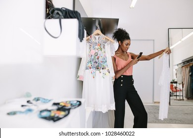 Fashion designer taking photograph of a designer dresses in her fashion studio. Customer taking photograph of dress in a fashion clothes shop.