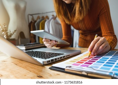 Fashion designer talking mobile phone and using laptop with digital tablet computer in modern studio