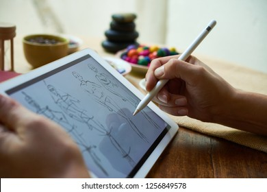 Fashion designer using modern tablet and drawing human figure sketches while working at table in studio