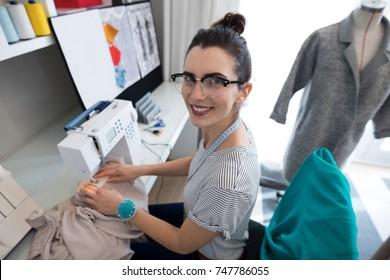 Fashion designer using sewing machine at home