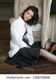 Fashion designer woman with brown hair in studio in white shirt making clothes like coco chanel
