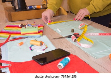 Fashion designer, Woman tailor posing at her workplace with cut fabric, free space on wooden work table. Garment industry, tailoring concept