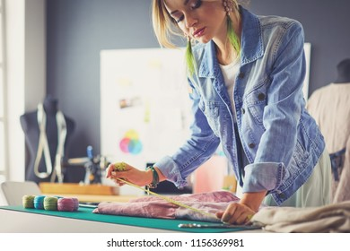 Fashion designer woman working on her designs in the studio