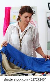 Fashion designer working in studio. Dressmaker woman