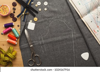 Fashion designer workspace top view. Sewing equipment, threads and buttons, pins and scissors on cloth squares with copy space