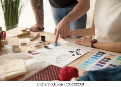 Fashion designers team choosing colors for new collection discussing sketches, dressmakers working on clothes creation using swatches pallet, teamwork in design studio concept, close up view