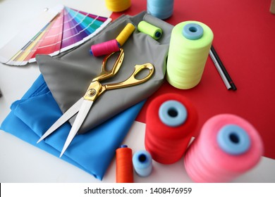 Fashion Designing Tailor Craftsmanship Concept. Fabric, Color Palette and Sewing Tools on Table. Needle Machine Bobbins Spools of Thread with Gold Scissors on Silk Piece. Designer Working Desk
