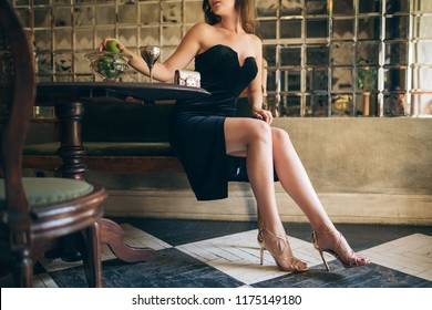 fashion details of elegant beautiful woman sitting in vintage cafe in black velvet dress, rich stylish lady, elegant trend, long skinny legs, wearing high heeled sandals shoes, footwear