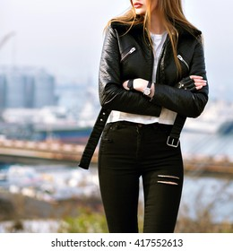 Fashion details, model posing near city port, grunge urban style, black leather jacket, rack style. long blonde hairs.