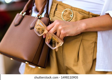 Fashion details of style woman wearing linen pants, caramel small vintage leather bag and holding modern clear glasses, smart casual business style, warm colors, mid season.