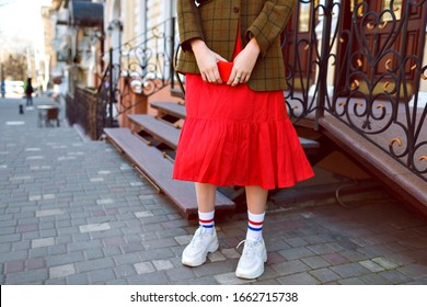 Fashion details of stylish hipster blogger woman posing on the street, wearing white ugly sneakers, long funny socks, red midi skirt and oversized jacket, mid season time.