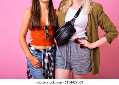 Fashion details stylish picture, two woman hugs and posing together in studio, casual trendy 90s style outfits, jeans, crop top, plated shirt, vintage jacket, bum bag and sunglasses.