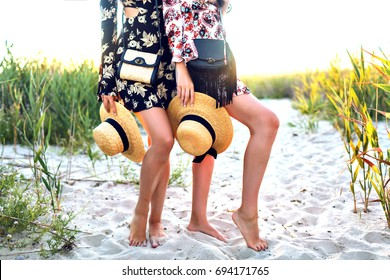 Fashion details, two woman with long legs posing on field, boho style dress, holding straw hats and bags, holiday vacation vibe.