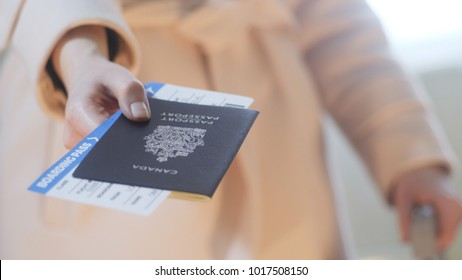 Fashion dressed girl with a suitcase holds Canadian passport and boarding pass in her hand