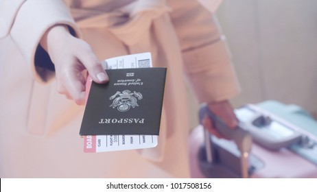 Fashion dressed girl with a suitcase holds American passport and boarding pass in her hand