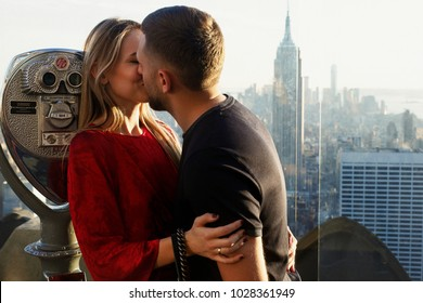Fashion dressed young couple stands on the top of Rockafeller Center in New York city