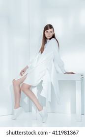 Fashion editorial shot in studio with white background. Beautiful model posing in total white clothes.