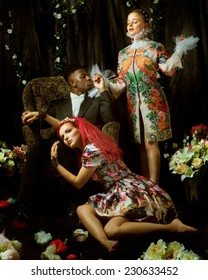 Fashion editorial with two women and one man between flowers