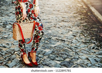 Fashion elements: woman wearing floral printed jumpsuit, red shoes, wrist watch, holding straw bag, posing in street. Photo without face. Copy, empty space for text