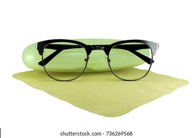Fashion eyeglasses resting on a yellow cloth and a box for entering. On white background with clipping path.