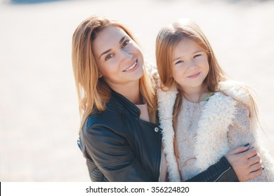 Fashion family concept - stylish mother and child wear. A portrait of a happy family: a young beautiful woman with her little cute daughter. Young daughter hugs mother in autumn city outdoor