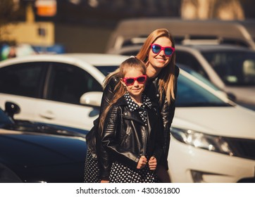Fashion family concept - stylish mother and child wear a leather jacket and sunglasses in the city