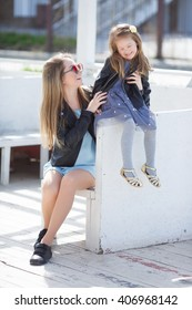 fashion family. woman with child girl in family fashionable look having fun outdoor. Fashion young mother and child daughter wearing a sunglasses