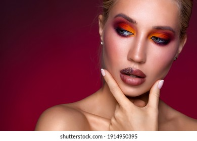 Fashion fashionable beautiful woman bright colored makeup. Glamour passion multi-colored makeup. Close-up portrait colourful. style, abstract colorful makeup, artistic design. Black background
