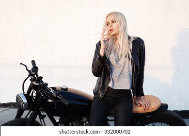 Fashion female biker girl. Young blonde woman sitting on vintage motorcycle and smoking cigarette. Outdoors lifestyle portrait