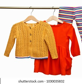 Fashion female child's dress and knitted cardigan (jacket) with leggings (tights, child's pants) hanging on clothesline isolated on white background for spring and summer wardrobe