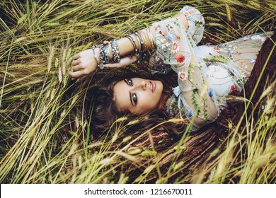 Fashion female model posing in a field. Contemporary bohemian style.