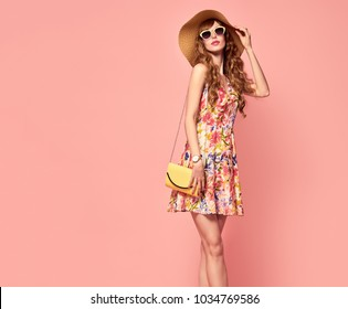 Fashion. Female model with Wavy Hairstyle in Trendy Sunglasses. Young Beautiful European girl Posing in Studio on coral. Portrait of Slim fashionable woman. Summer Outfit.