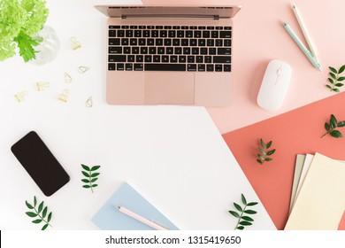 Fashion female office desk table with spring flowers and leaves, laptop, notebook, calculator, stationary, mobile phone and other office. Top view and flat lay with copy space
