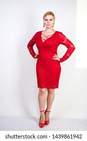 fashion female in red lace dress standing alone. plus size blonde woman with short hair and chubby body posing in evening middle length dress on white studio background.