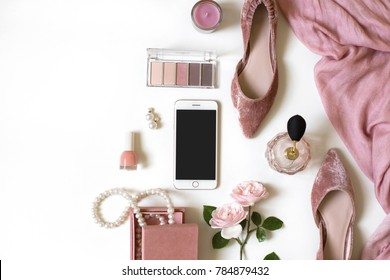 Fashion feminine blogger concept. Minimal set of woman accessories on white background. Still life of pink objects: rose, cosmetics, perfume, jewellery, shoes, smart phone mockup with empty screen