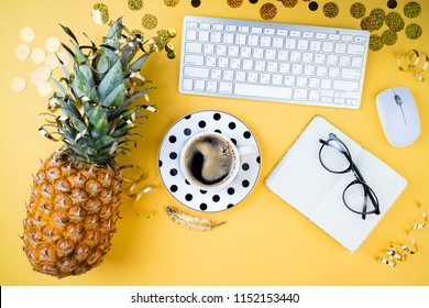 Fashion feminine home office, workspace flat lay. Pineapple, coffee cup, golden confetti, women's accessories, glasses and notebook on yellow table. Festive female background.  Top view