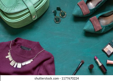 Fashion flat lay on the wooden turquoise background with cosmetics, shoes and dress. Top view concept frame. Copy space