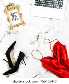 Fashion flat lay for social media with laptop. Red dress, black high heels, golden frame, notebook. Office desk