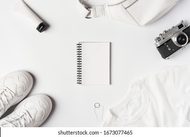 Fashion flat lay with white t shirt, sneakers, waist bag and accessories, monochrome list and shopping concept, casual look. Copy space, top view