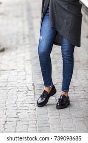 Fashion forward clothing with asymmetrical top, skinny jeans and retro style loafers.  Model posing for pictures outside on the grey pavement. Skinny jeans with leather vintage style shoes.