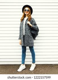 Fashion full-length woman in gray coat, black round hat posing on white wall background on street city