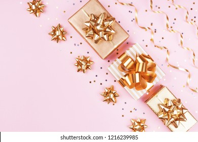 Fashion gift or present boxes with golden bows, serpentine and star confetti on pink pastel table top view. Flat lay composition for birthday, christmas or wedding.