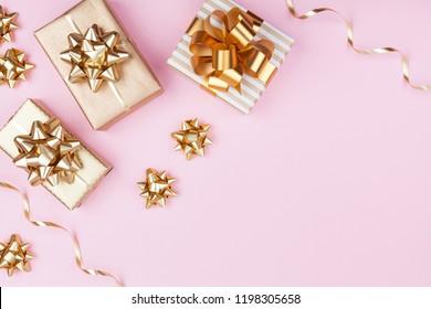 Fashion gifts or presents boxes with golden bows on pink pastel background top view. Flat lay composition for birthday, christmas or wedding.