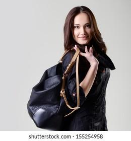 fashion girl, beautiful young woman posing at studio in black dress with bag