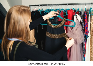 Fashion girl is choosing dress for night party. Female dressmaker holding hanger with dress. Woman working in fashion boutique. Stylist of showroom choosing clothing for new image.