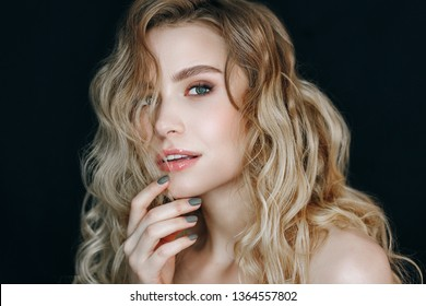 Fashion Girl Face Makeup Photography Portrait. Woman with White Skin Posing on Black Background. Model with Curly Hair and Open Mouse. Lady with Glossy Lip Make-up Head and Shoulders Shoot.